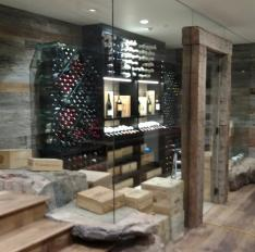 Glass Unlimited Custom glass wine room cut into stone with wood beams.