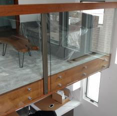 Glass Unlimited glass railing with wood cap rail and stand-offs.